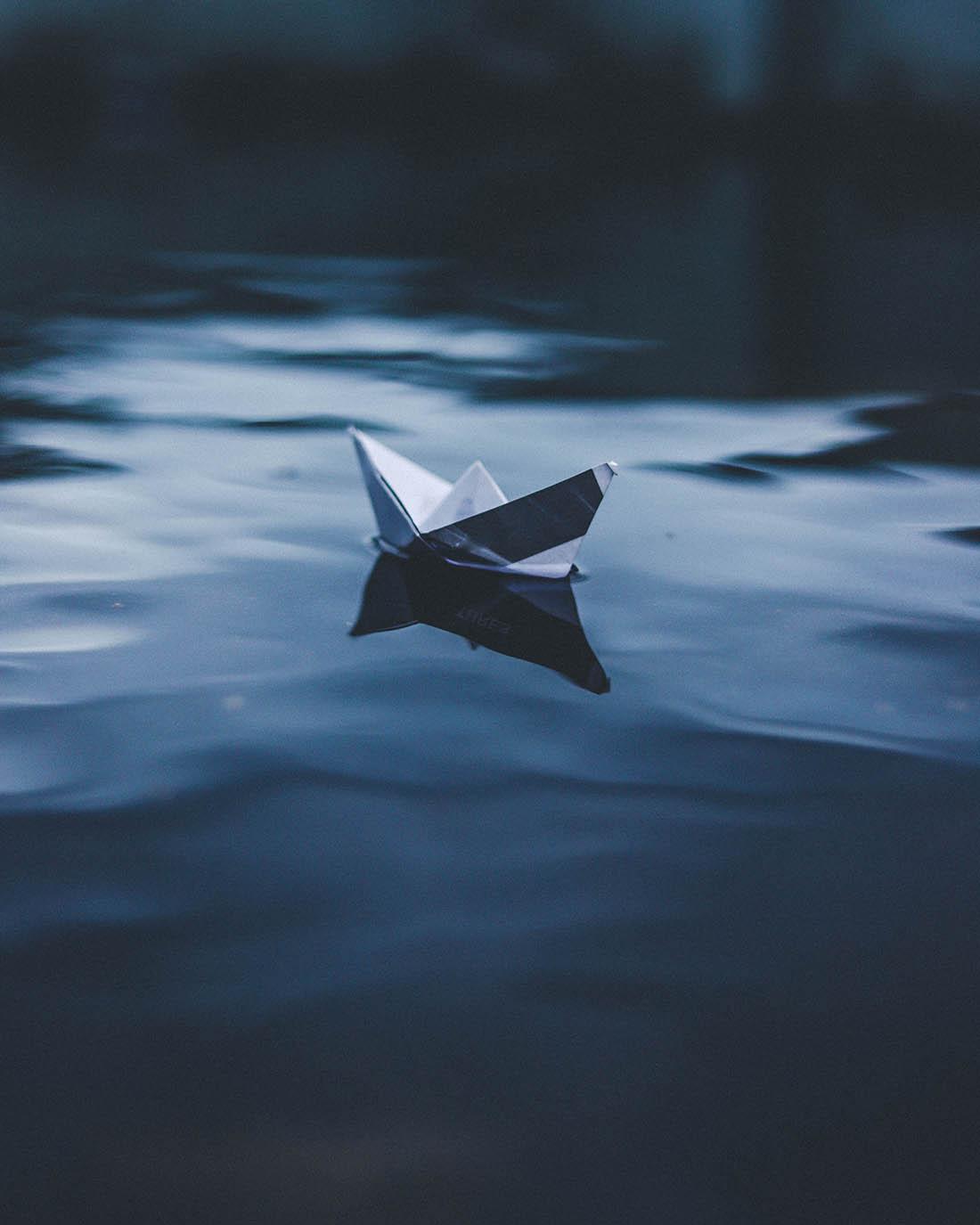 Origami-båt av trycksak i papper på vågigt vatten