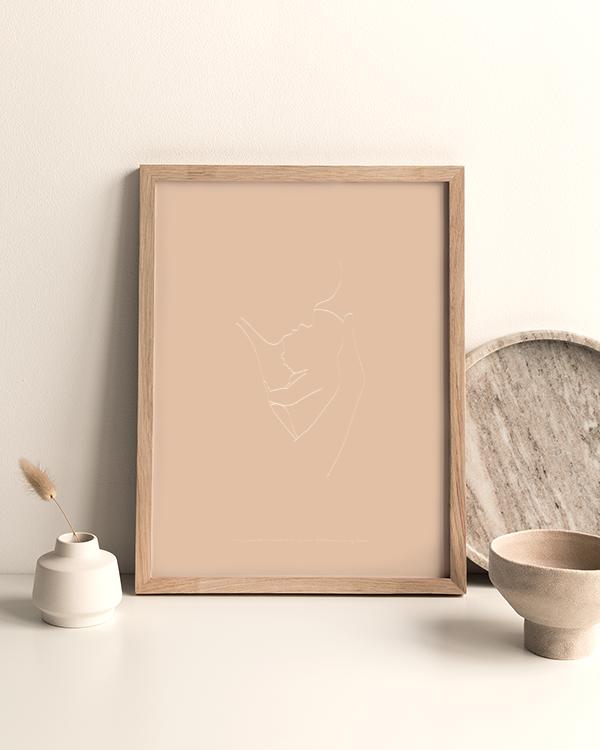 Sandfärgad poster med illustration av silhuett med baby i förälders famn, inramad stående på ett bord omgiven av dekorationer i ljusa naturfärger