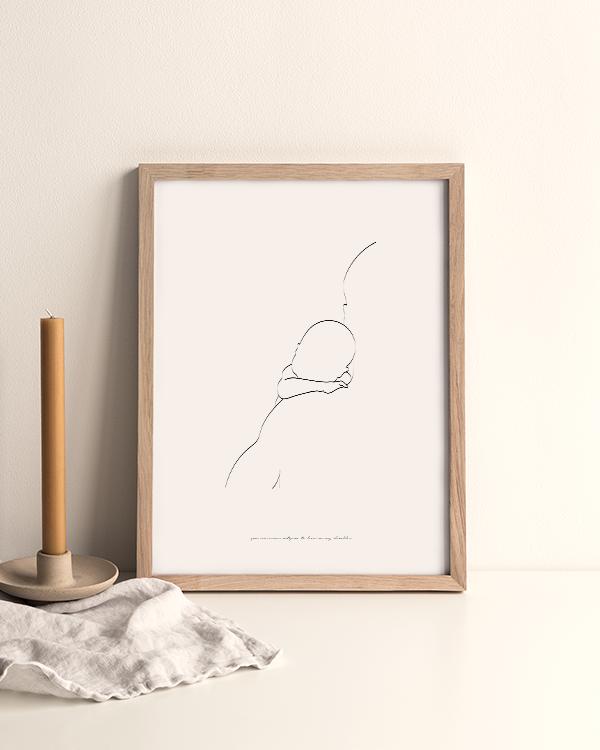 Svartvit poster med illustration av silhuett med baby vilande på förälders axel, inramad stående på ett bord omgiven av ett ljus i beige enkel ljusstake och en naturfärgad linneduk